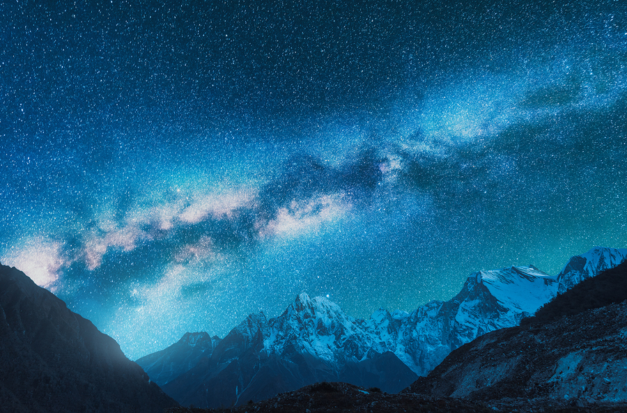 Milky Way And Snowy Mountains. Fantastic View With Mountain Ridg